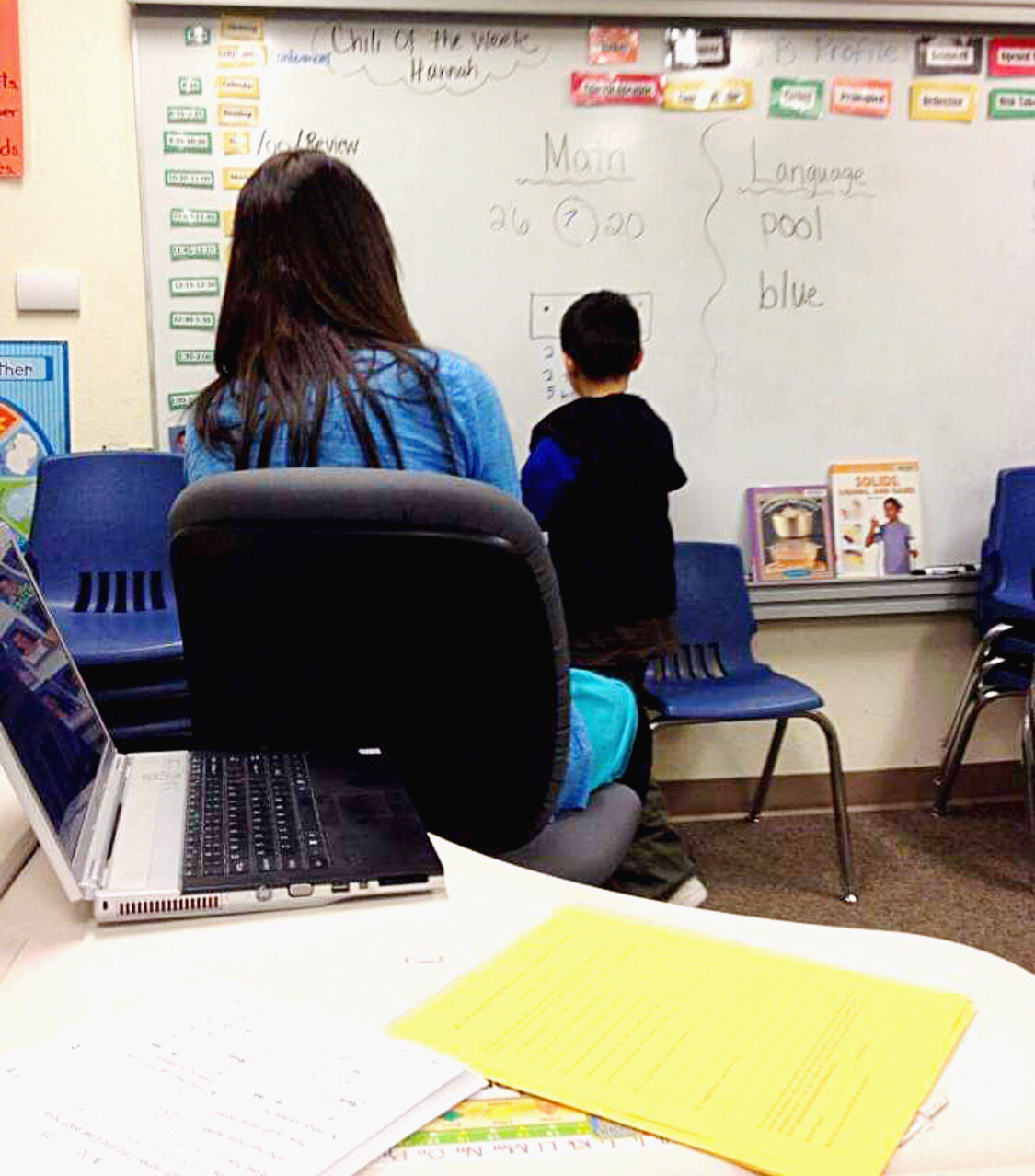 A boy standing in front of the school board as his teacher watches.