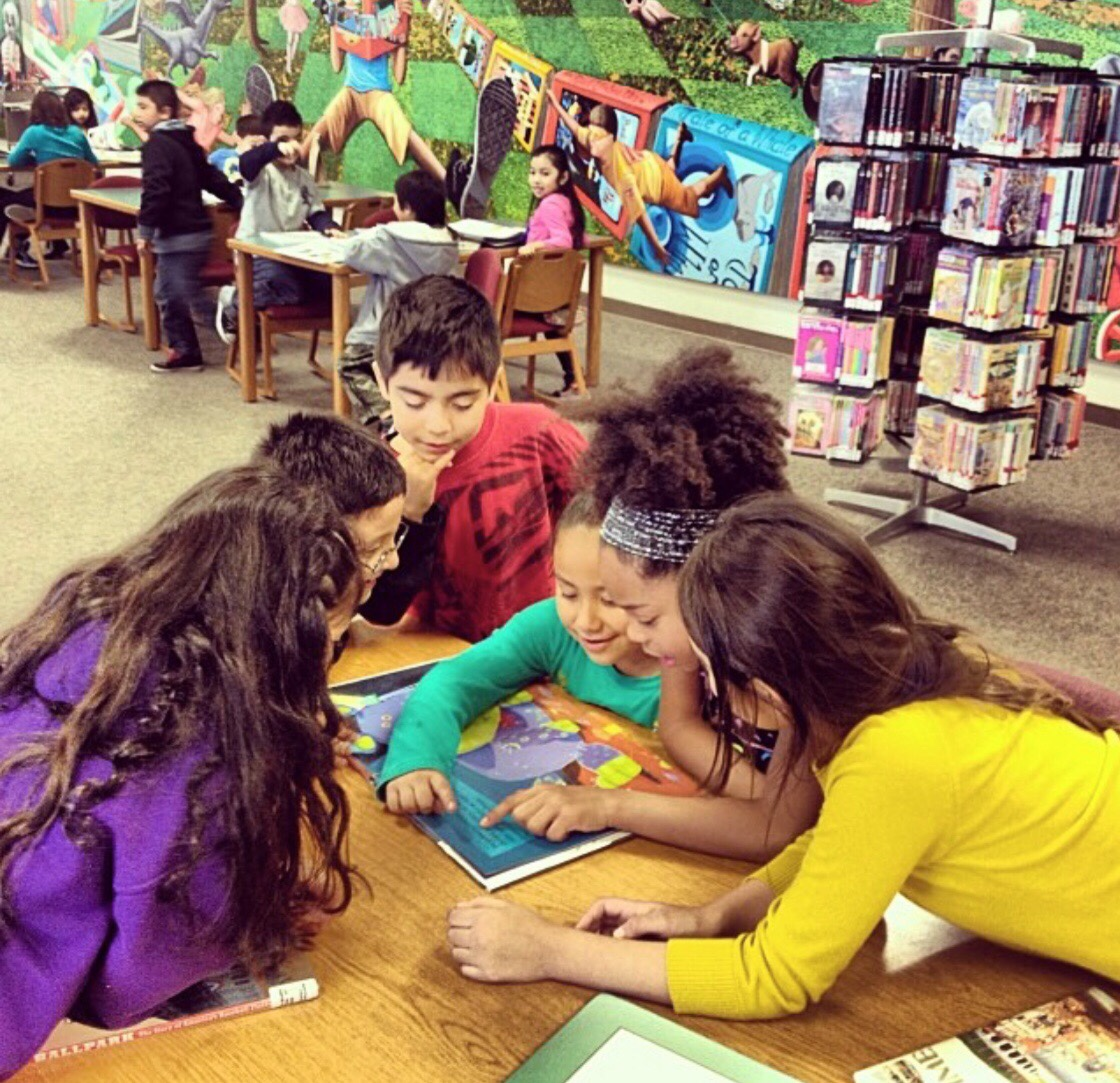 several children gathered around a table reading a book