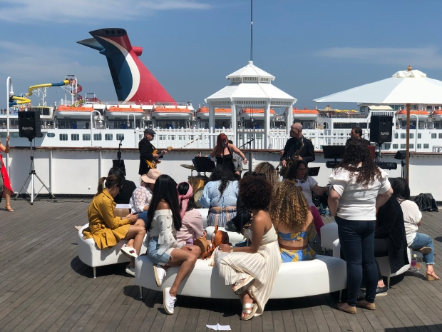 Several women seated in front of a live band on an open deck of The Queen Mary