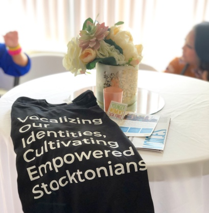 VOICES t-shirt laid into a table decorated with a white table cloth and flower centerpiece.