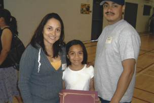 Mother, daughter, and father pose for a photo. Daughter is holding an award certificate