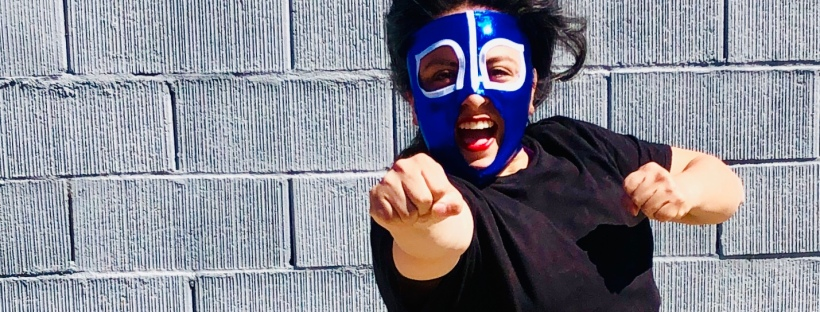Woman wearing a blue luchadora mask in a superhero stance