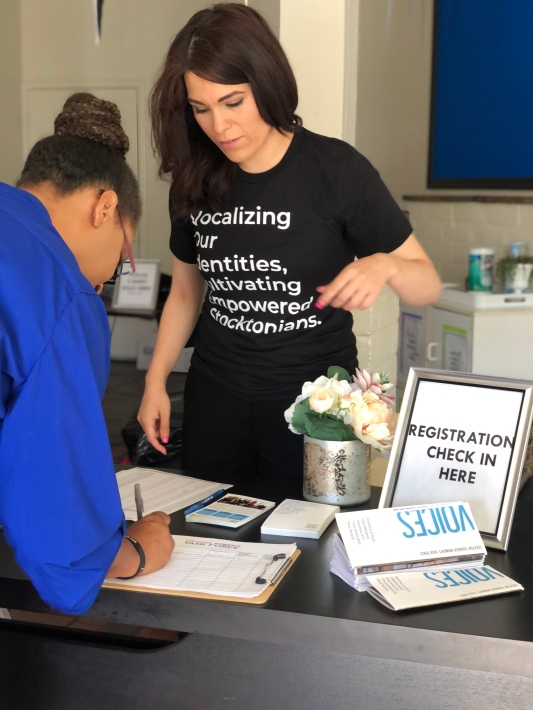 A woman signs in at the VOICES: Childcare Launch event.