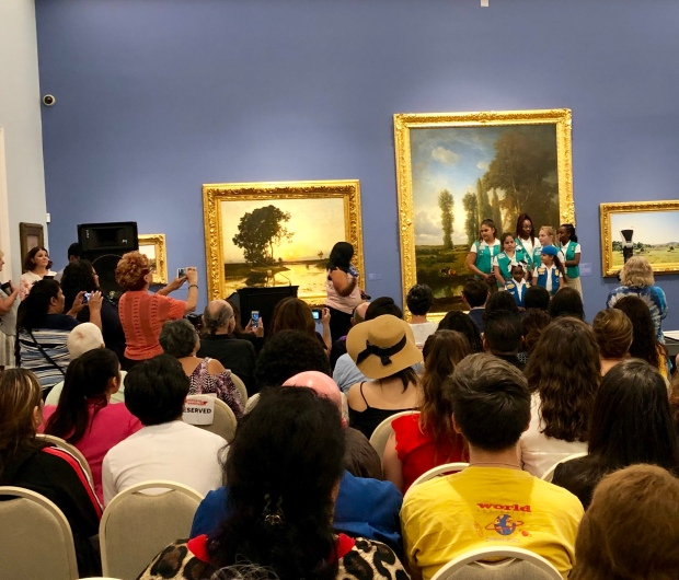 Rows of people seated to watch a group of Girl Scouts perform.