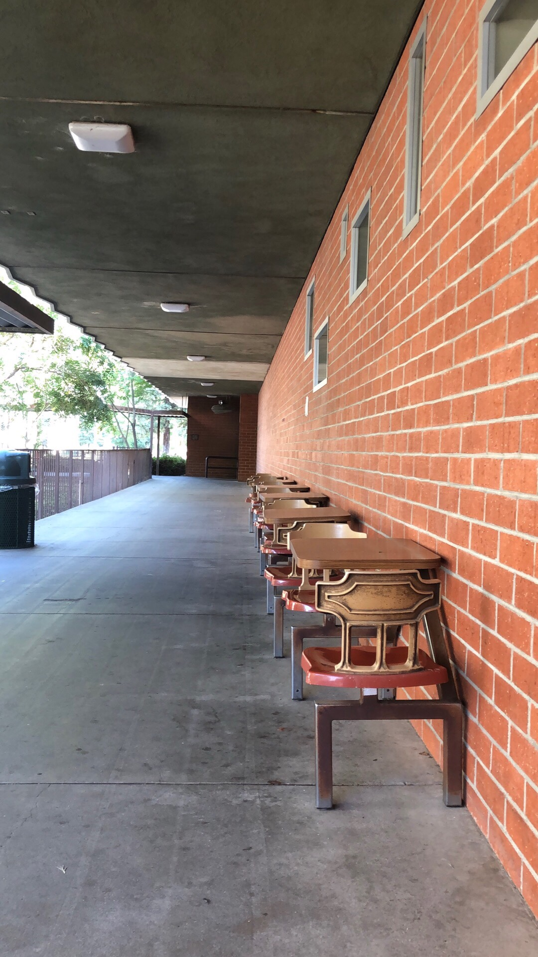 Exterior of the San Joaquin General Hospital cafeteria. Tables and chairs lined up against a brick wall.