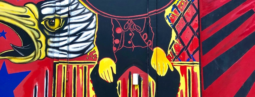Vibrant mariachi mural in reds, yellows, behind a classic black mariachi suit.
