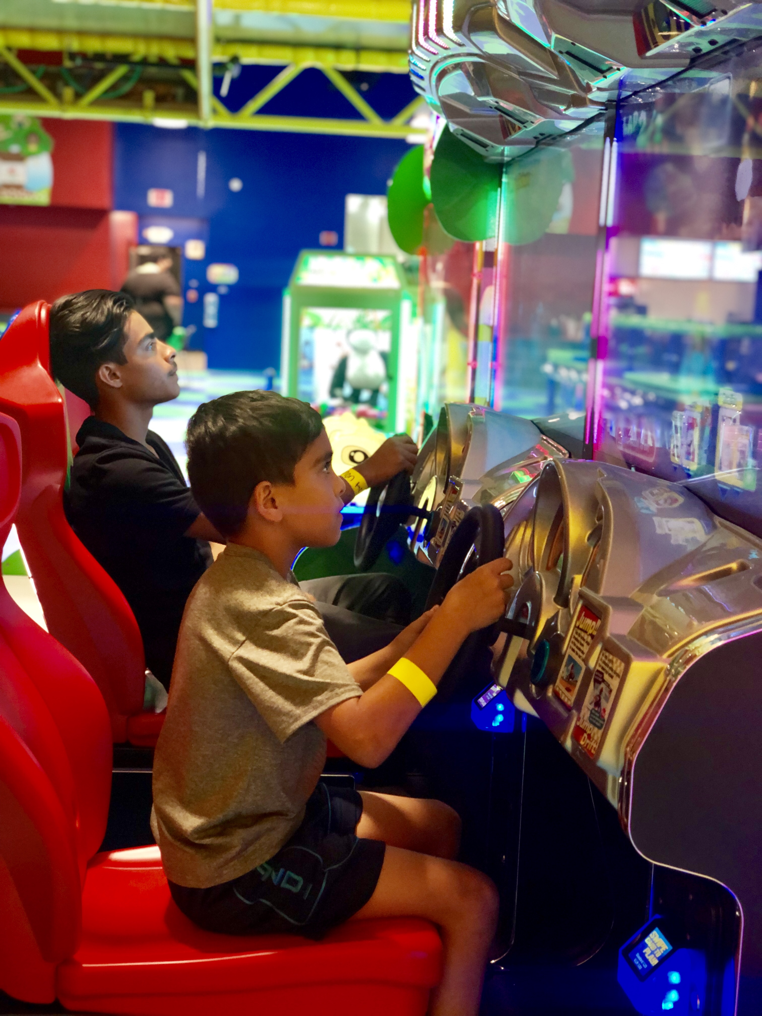 Two boys playing a racing arcade game
