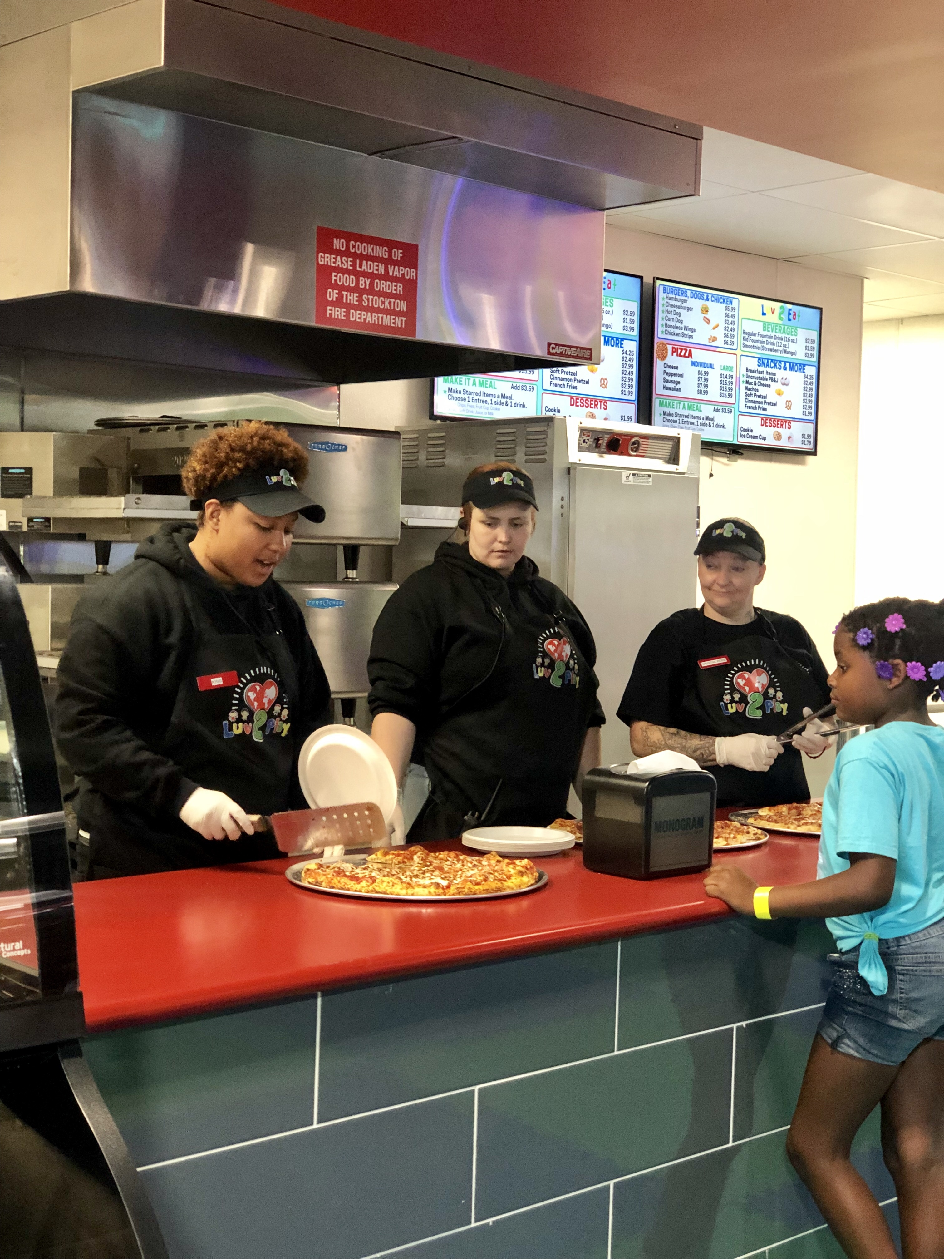 women serving pizza to a young girl
