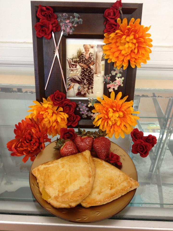 Framed photo of woman. Flowers pasted to photo frame. Plate of strawberries and empanadas.