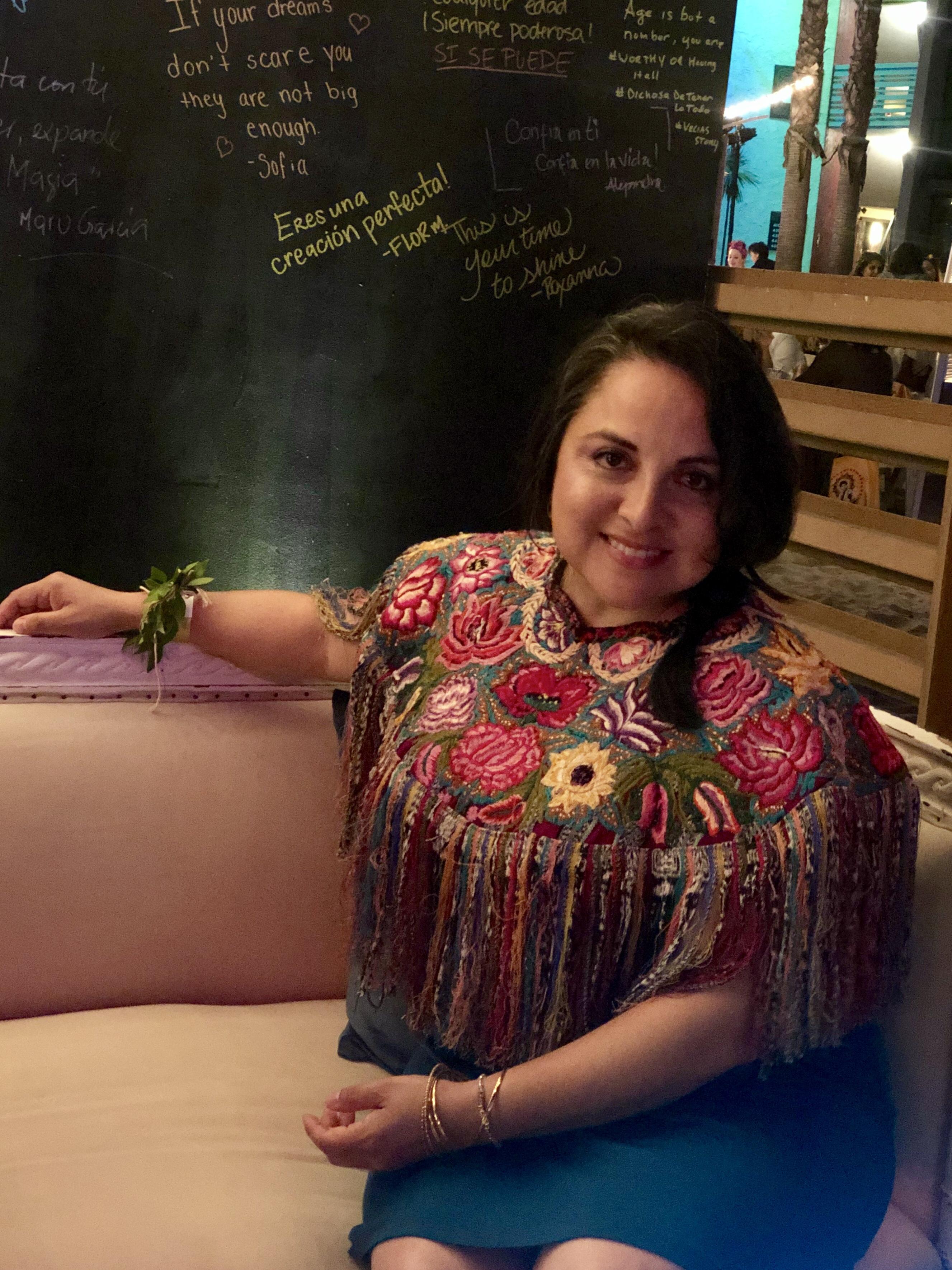 Woman sitting wearing a huipil